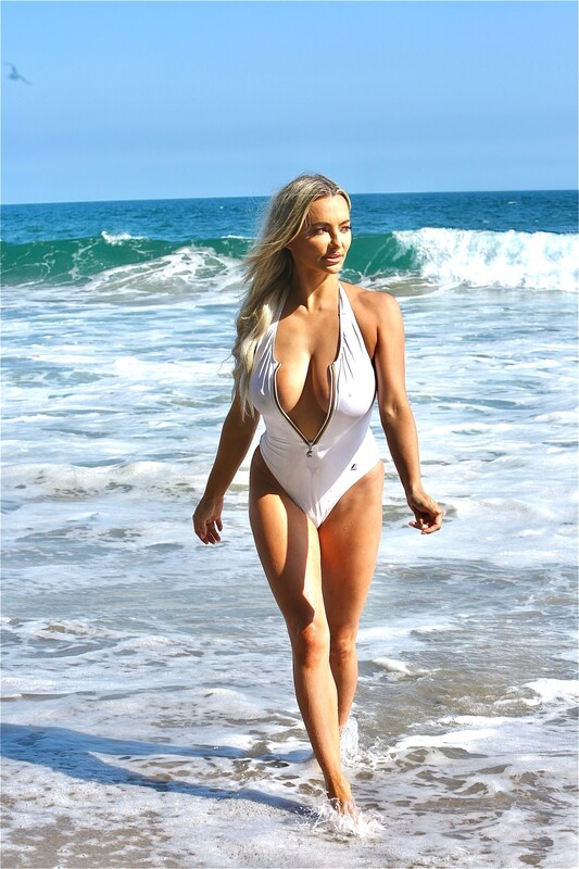 busty blonde lady Lindsey Pelas in white 1 piece swimsuit